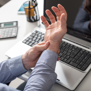 Man with carpal tunnel holding wrist