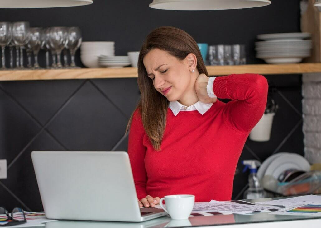 Woman in red sweater working at laptop with neck pain, neck discomfort, back pain, coffee, papers on desk