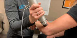 Orthopedic Institute physical therapist applies shockwaves to arm of female patient near the elbow using a handheld Radial Pulse Therapy tool to alleviate pain due to plantar fasciitis.