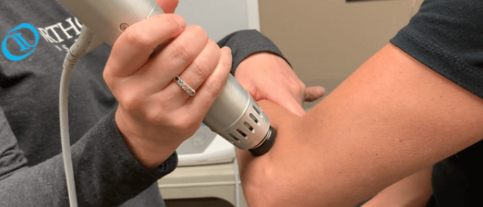 A physical therapist utilizes the handheld Radial Pulse Therapy system as a treatment solution for the pain in the patient's elbow from tennis elbow or elbow epicondylitis.