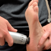 A physical therapist manipulates the bottom of a patient's foot using a handheld Radial Pulse Therapy tool to alleviate pain due to plantar fasciitis.